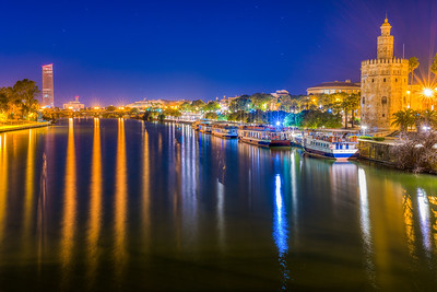 The Guadalquivir river and the Gold Tower (12th century) at night, Seville, Spain