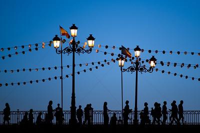Pedestrians on the Triana bridge during  the Vela de Santa Ana festival, Seville, Spain.