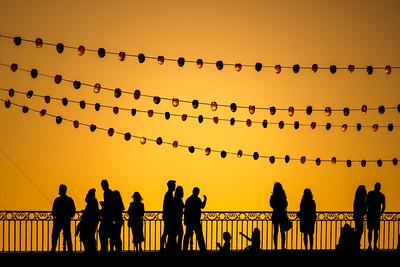 Pedestrians on the Triana bridge during the Vela de Santa Ana festival, Seville, Spain