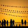 Pedestrians on the Triana bridge during the Vela de Santa Ana festival, Seville, Spain