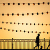 Pedestrians on Triana bridge during Vela de Santa Ana festival, Seville, Spain
