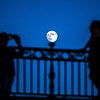 Couple taking pictures under moonling on the Triana bridge, Seville, Spain.