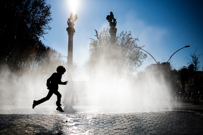 Little girl playing in front of a fountain, Alameda de Hercules square, Seville, Spain