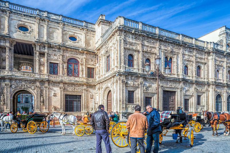 Horse drawn carriages waiting for visitors in front of the plateresque City Hall, San Francisco Square, Seville, Spain