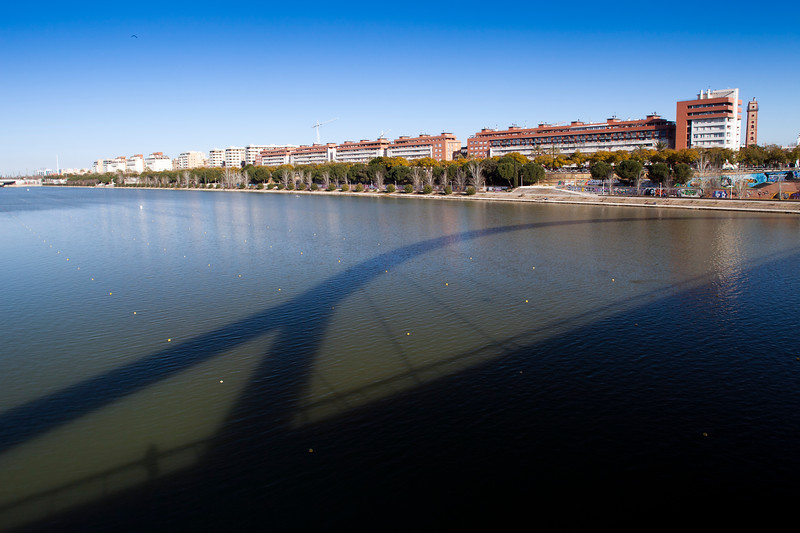 Guadalquivir river from Barqueta bridge, which casts its shadow on the water, Seville, Spain
