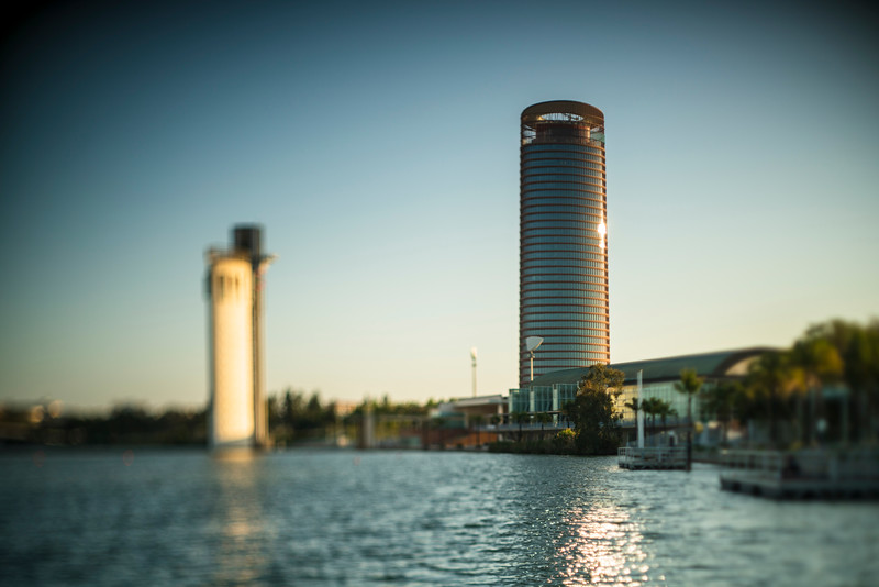 Torre Sevilla skyscraper (right) and Schindler tower (left, out of focus) by the Guadalquivir river, Seville, Spain. Shallow depth of field achieved by tilting the focal plane of the lens.