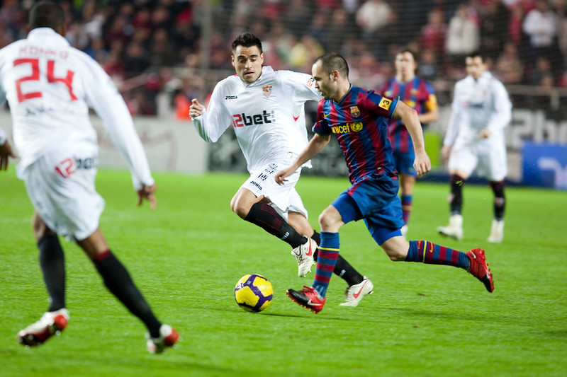 Andres Iniesta controlling the ball surrounded by opponent players. Spanish Cup game between Sevilla FC and FC Barcelona, Ramon Sanchez Pizjuan stadium, Seville, Spain, 13 January 2010