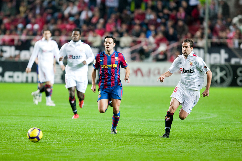 Xavi pursued my Fernando Navarro. Spanish Cup game between Sevilla FC and FC Barcelona, Ramon Sanchez Pizjuan stadium, Seville, Spain, 13 January 2010