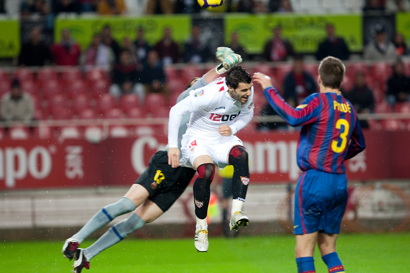Alvaro Negredo trying to head the ball between Pinto and Pique. Spanish Cup game between Sevilla FC and FC Barcelona, Ramon Sanchez Pizjuan stadium, Seville, Spain, 13 January 2010