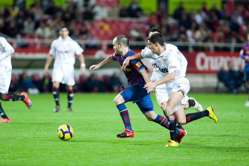 Iniesta and Navas fighting for the ball. Spanish Cup game between Sevilla FC and FC Barcelona, Ramon Sanchez Pizjuan stadium, Seville, Spain, 13 January 2010