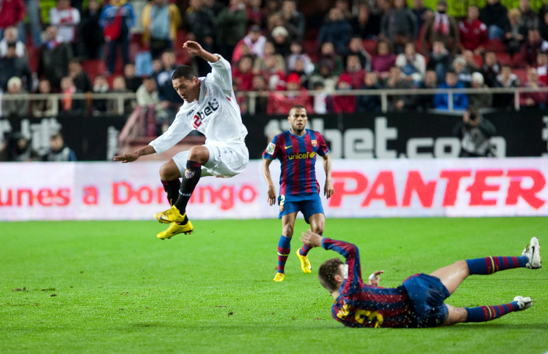Adriano jumping over Pique. Spanish Cup game between Sevilla FC and FC Barcelona, Ramon Sanchez Pizjuan stadium, Seville, Spain, 13 January 2010