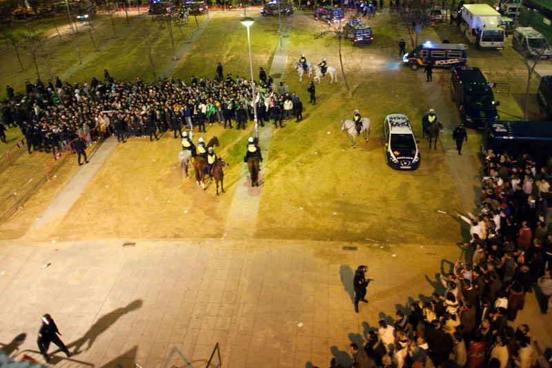 Riot policemen escorting Real Betis fans when they arrive to Sevilla FC stadium. Taken before the football derby between Sevilla FC and Real Betis Balompie that took place in Sanchez Pizjuan stadium on 7 Feb 2009, Seville, Spain.