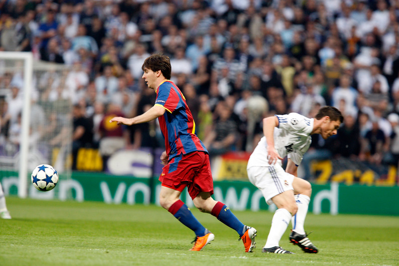 Messi with the ball dribbling Xabi Alonso, UEFA Champions League Semifinals game between Real Madrid and FC Barcelona, Bernabeu Stadiumn, Madrid, Spain