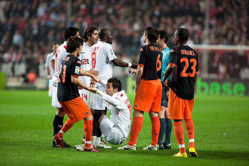 Silva helps Negredo to get up among other players. Spanish Liga game between Sevilla FC and Valencia CF. Sanchez Pizjuan stadium, Seville, Spain, 31 January 2010
