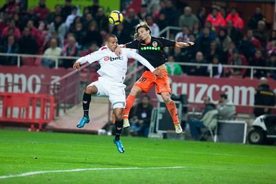 Luis Fabiano and Alexis jumping for the ball. Spanish Liga game between Sevilla FC and Valencia CF. Sanchez Pizjuan stadium, Seville, Spain, 31 January 2010