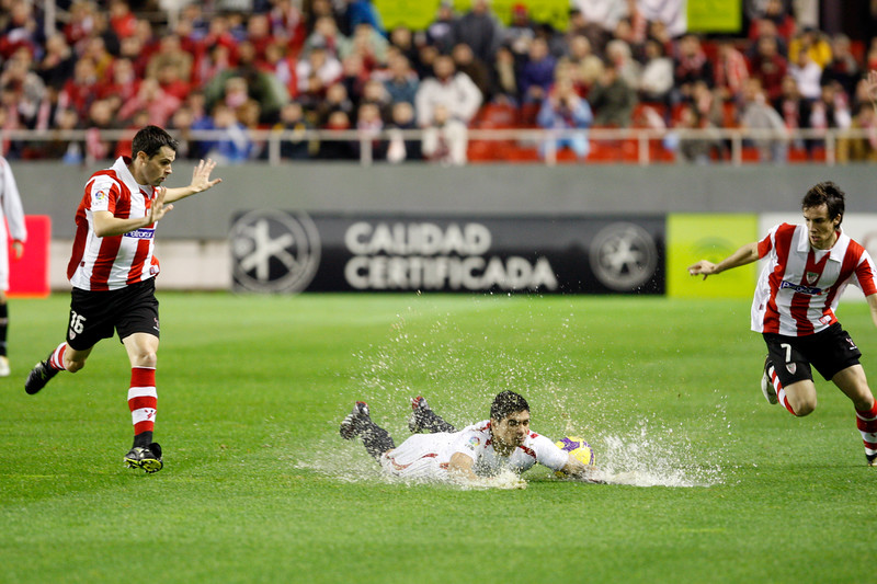 Orbaiz (left) and David Lopez (right) looking at Renato slipping on the damp ground. Taken in the Sanchez Pizjuan stadium on 4 Feb 2009 during the King's Cup semifinal game between the football teams Sevilla FC and Athletic Club of Bilbao, town of Seville, autonomous community of Andalusia, southern Spain
