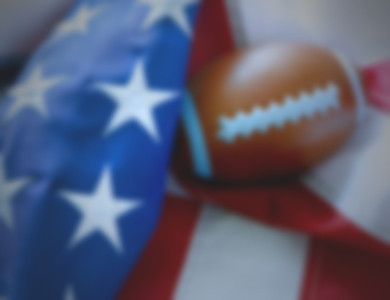 Background blur of a toy American football resting in the folds of a United States flag. Side lighting used for dramatic effect. Good for controversy between the football league and patriotism