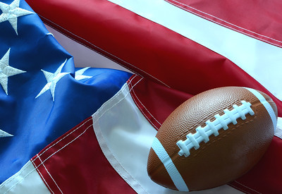 A toy American football resting in the folds of a United States flag. Side lighting used for dramatic effect. Good for controversy between the football league and patriotism