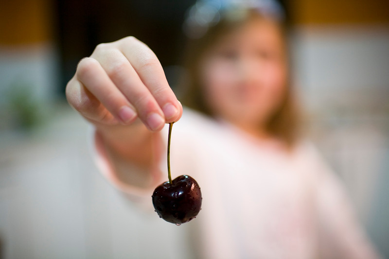 Young girl holding a cherry, Seville, Spain