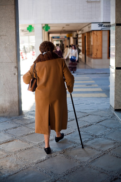 Old lady walking down the street, Seville, Spain