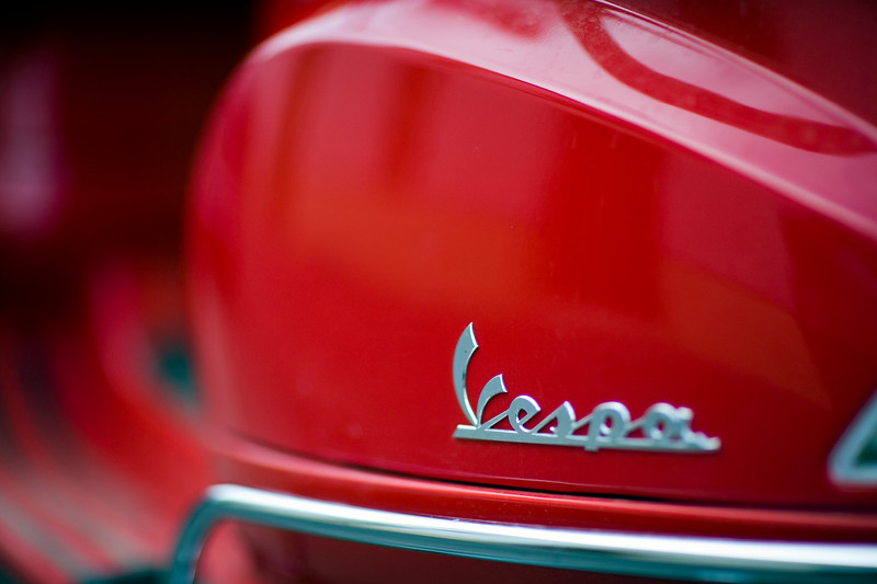 The Vespa brand logo from a red scooter, Seville, Spain