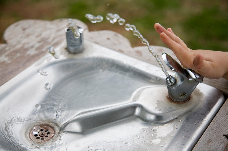 The hand of a child pushing the button of a water fountain