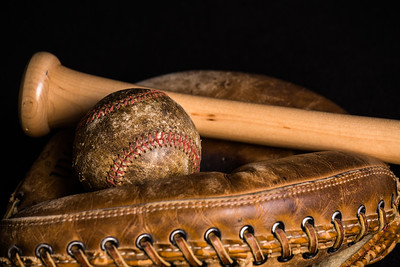 Stained old baseball resting on a catchers mitt with a new bat.