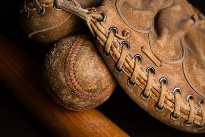 Catchers mitt with old baseball and bat.
