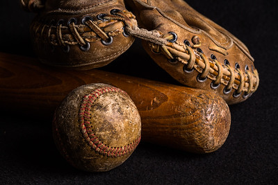 Nostalgic baseball gear old and worn from years of games.