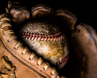 Dramatic side lighting on old baseball caught in worn out mitt.