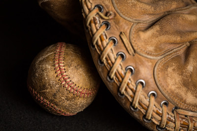 Baseball shadowed by old mitt with worn stitching and stained with years of games.