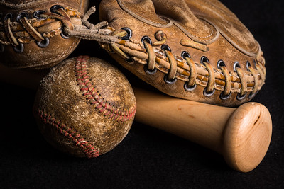 Old style mitt, badly stained and scratched baseball, and brand new shiny bat.