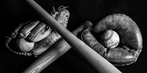 Black and White of two baseballs, mitt, and bats laid out on black