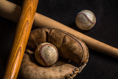 Baseball equipment from a childhood long ago. The gear is well used and scratched up.