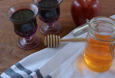 Detail of tabletop scene of Jewish celebratory items for Rosh Hashanah or Yom Kippur. Includes wine in amethyst glass goblets, honey and an apple on a wooden table