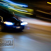 A panning shot of a speeding car at night time.