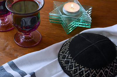 Detail of tabletop scene of Jewish celebratory items for Rosh Hashanah or Yom Kippur. Includes wine in amethyst glass goblets, a kippah and a star of david candle on wooden table. Side lighting used.