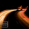A long exposure night shot of a freeway turn.  The lights will be streaking.