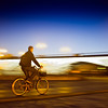 Panning shot of a cyclist by Tirana Bridge, Seville, Spain