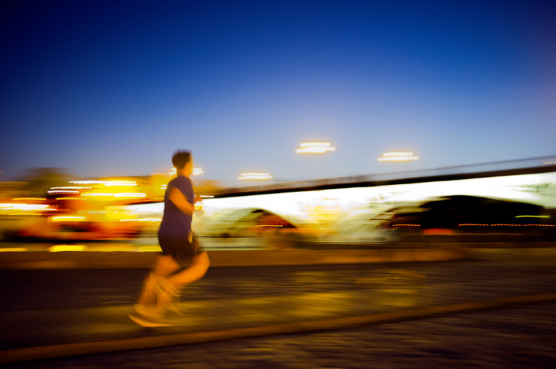 Panning shot of a runner by Triana Bridge at dusk, Seville, Spain