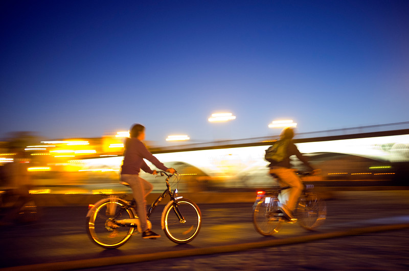 Panning shot of cyclists by Tirana Bridge, Seville, Spain