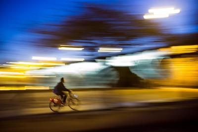 Panning shot of a cyclist by Tirana Bridge, Seville, Spain