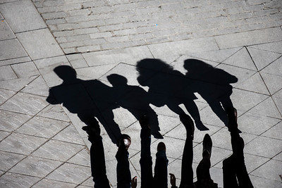 The shadows and silhouettes of a family group (father, mother, son and daughter) walking down the street