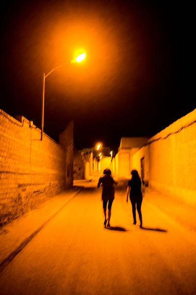 Two girls walking down a lonesome street by night, La Solana, Spain