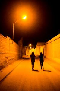 Two girls walking down a lonesome street by night, La Solana, Spain
