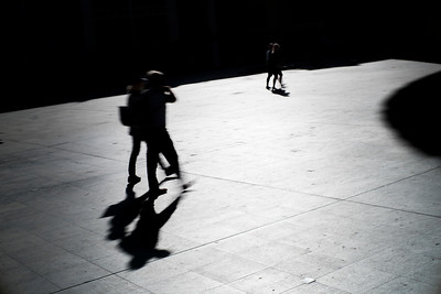 Silhouetted pedestrians on a square, Seville, Spain