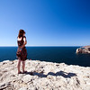 Girl looking at the Atlantic Ocean, cabo Sao Vicente (Cape Saint Vincent), town of Sagres, municipality of Vila do Bispo, district of Faro, region of Algarve, southwestern Portugal