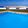 Swimming pool of Pousada Infante de Sagres Hotel with Sagres point on the background. Town of Sagres, municipality of Vila do Bispo, district of Faro, region of Algarve, southwestern Portugal