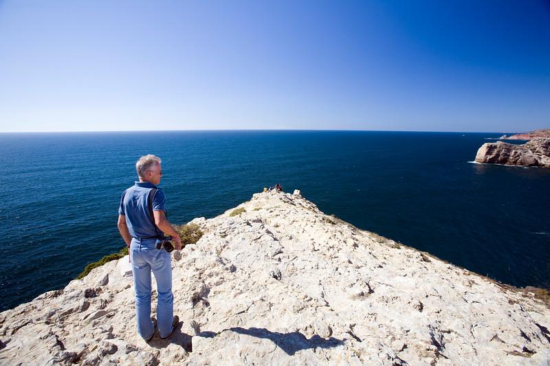 Man looking at the Atlantic Ocean, cabo Sao Vicente (Cape Saint Vincent), town of Sagres, municipality of Vila do Bispo, district of Faro, region of Algarve, southwestern Portugal