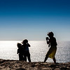 Mother taking pictures of her children on the top of a cliff, Sao Vicente Cape, Portugal.